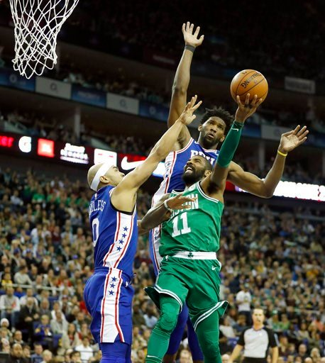 (AP Photo/Kirsty Wigglesworth). Boston Celtics guard Kyrie Irving, center, goes up for a layup while being blocked by Philadelphia 76ers guard Jerryd Bayless, left, during an NBA basketball game between the Boston Celtics and the Philadelphia 76ers at ...
