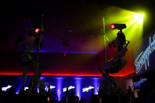 (AP Photo/Jae C. Hong). Two pole-dancing robots built by British artist Giles Walker perform at a gentlemen's club Monday, Jan. 8, 2018, in Las Vegas. The event was held to coincide with CES International.
