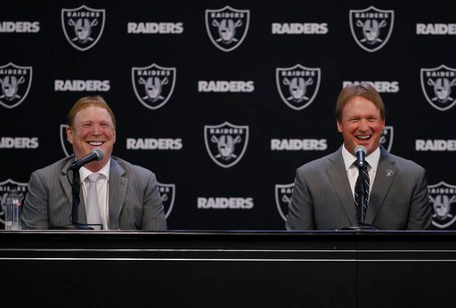 (AP Photo/Marcio Jose Sanchez). Oakland Raiders new head coach Jon Gruden, right, smiles as he listens to a question from former Raiders player Charles Woodson, as he sits next to owner Mark Davis during an NFL football press conference Tuesday, Jan. 9...