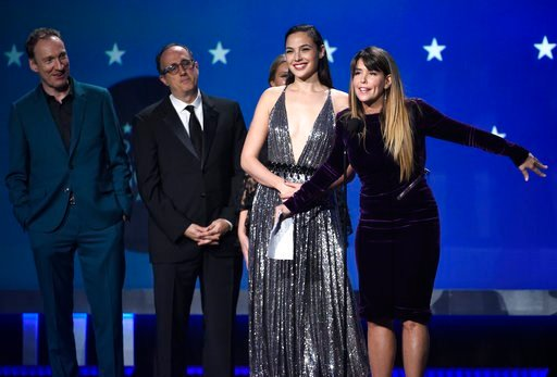 "(Photo by Chris Pizzello/Invision/AP). Gal Gadot, center, Patty Jenkins and the crew of ""Wonder Woman"" accept the award for best action movie at the 23rd annual Critics' Choice Awards at the Barker Hangar on Thursday, Jan. 11, 2018, in Santa Monica, Ca..."
