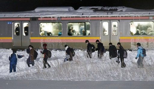 (Suo Takekuma/Kyodo News via AP). Passengers of a stranded train walk beside a railway track in Sanjo, Niigata prefecture, north of Tokyo early Friday, Jan. 12, 2018. A Japanese railway official says about 430 people were stuck on the train overnight b...