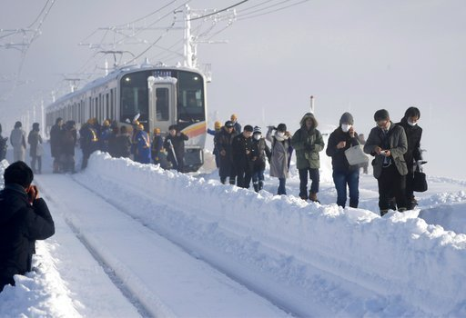 (Suo Takekuma/Kyodo News via AP). Passengers take shelter from a stranded train in Sanjo, Niigata prefecture, north of Tokyo Friday, Jan. 12, 2018. A Japanese railway official says about 430 people were stuck on the train overnight because of heavy sno...