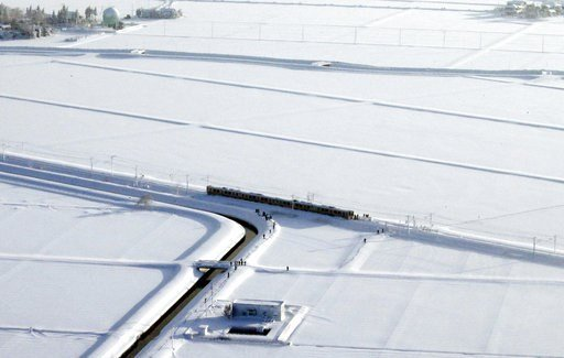 (Yohei Fukai/Kyodo News via AP). A train, center, is stranded in Sanjo, Niigata prefecture, north of Tokyo Friday, Jan. 12, 2018. A Japanese railway official says about 430 people were stuck on the train overnight because of heavy snow that blanketed m...