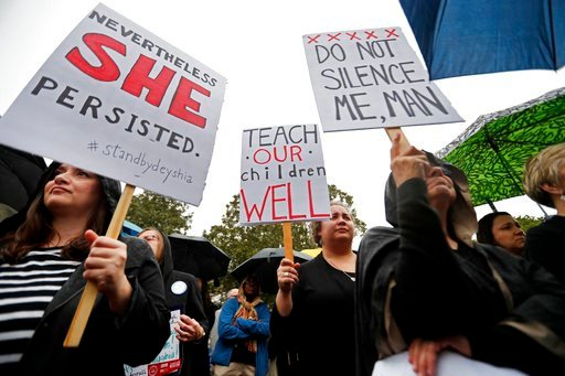 (AP Photo/Gerald Herbert). People hold signs at a rally for school teacher Deyshia Hargrave, who was arrested while speaking against the superintendent's pay raise at an education board meeting earlier this week, in Abbeville, La.