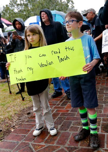 (AP Photo/Gerald Herbert). Sydney Brown, 6, and Josiah Brevis, 8, hold a sign at a rally for school teacher Deyshia Hargrave, who was arrested while speaking against the superintendent's pay raise at an education board meeting earlier this week.