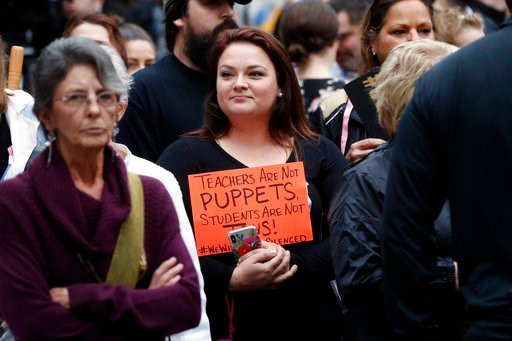 (AP Photo/Gerald Herbert). Alicia LaSalle, a Vermilion Parish school teacher, holds a sign in solidarity at a rally in Abbeville, La., Thursday, Jan. 11, 2018.