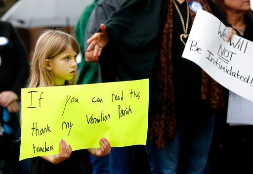 (AP Photo/Gerald Herbert). Sydney Brown, 6, holds a sign at a rally for school teacher Deyshia Hargrave, who was arrested while speaking against the superintendent's pay raise at an education board meeting earlier this week, in Abbeville, La.