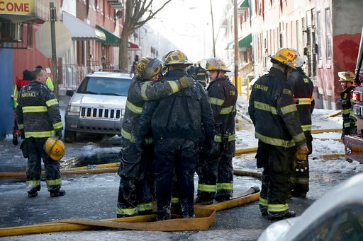 (Tim Tai/The Philadelphia Inquirer via AP). In this Saturday, Jan. 6, 2018, photo, firefighters embrace as their colleagues battle a row home fire in Philadelphia. A veteran firefighter was fatally injured Saturday when a burning row home collapsed in ...