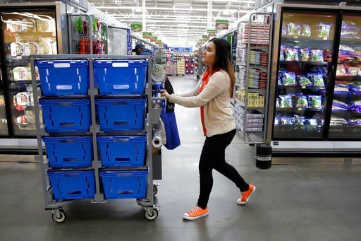 (AP Photo/Julio Cortez). In this Thursday, Nov. 9, 2017, photo, Laila Ummelaila, a personal shopper at the Walmart store in Old Bridge, N.J., pushes a cart with bins as she shops for online shoppers.