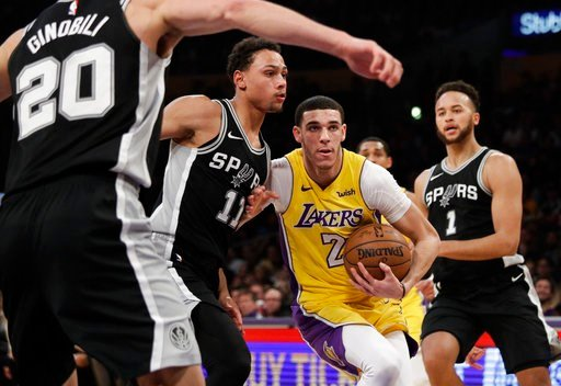 (AP Photo/Jae C. Hong). Los Angeles Lakers' Lonzo Ball, center right, is defended by San Antonio Spurs' Bryn Forbes during the first half of an NBA basketball game Thursday, Jan. 11, 2018, in Los Angeles.