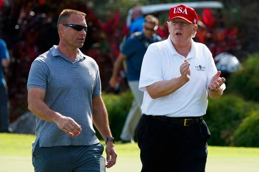 (AP Photo/Evan Vucci, File). In this Friday, Dec. 29, 2017, file photo, President Donald Trump walks with Gene Gibson, commanding officer at Coast Guard Station Lake Worth Inlet, as he arrives to meet with members of the U.S. Coast Guard.