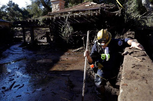 (AP Photo/Marcio Jose Sanchez). Alex Broumand of the Montecito Fire Department walks in mud in front of homes damaged from storms in Montecito, Calif., Thursday, Jan. 11, 2018. Rescue workers slogged through knee-deep ooze and used long poles to probe ...