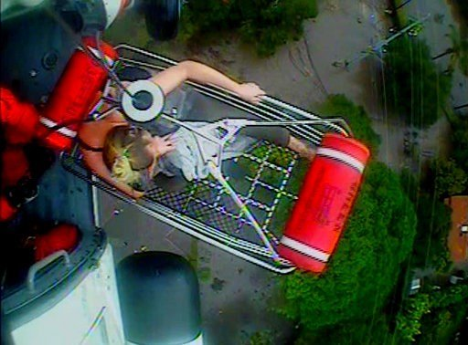 (U.S. Coast Guard via AP). In this Jan. 9, 2018, image from video provided by the U.S. Coast Guard, a woman and an infant are hoisted aboard a Coast Guard helicopter as they are rescued from a flood-damaged home in Montecito, Calif.