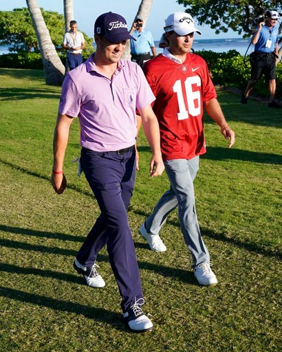 (AP Photo/Marco Garcia). Justin Thomas, left, walks with pairing partner Kevin Kisner, who wears a University of Alabama football jersey, off the 17th tee box during the first round of the Sony Open golf tournament, Thursday, Jan. 11, 2018, in Honolulu...