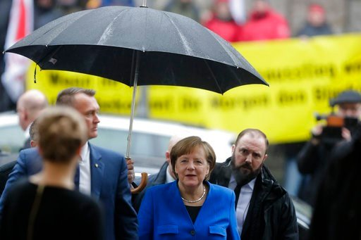 (AP Photo/Markus Schreiber). German Chancellor Angela Merkel, center, arrives for exploratory talks about a new German government between her Christian Unions block and the Social Democratic Party at the SPD headquarters in Berlin, Thursday, Jan. 11, 2...
