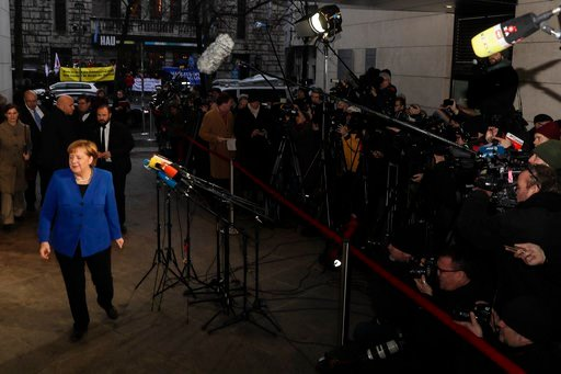 (AP Photo/Markus Schreiber). German Chancellor Angela Merkel, left, leaves after a statement prior to exploratory talks about a new German government between her Christian Unions block and the Social Democratic Party at the SPD headquarters in Berlin, ...