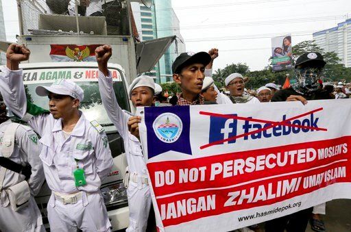 (AP Photo/Tatan Syuflana). A group of Muslims hold a banner during a rally outside the Facebook office in Jakarta, Indonesia, Friday, Jan. 12, 2018. Muslim hard-liners have staged protest against the social media giant Facebook in Indonesia's capital o...