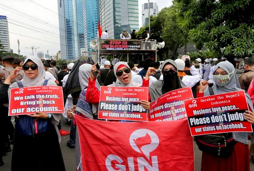 (AP Photo/Tatan Syuflana). A group of Muslim women hold posters during a rally outside the Facebook office in Jakarta, Indonesia, Friday, Jan. 12, 2018. Muslim hard-liners have staged protest against the social media giant Facebook in Indonesia's capit...