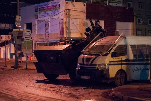 (AP Photo/Riadh Dridi). Security forces in an armoured vehicle patrol the district of Intilaka, north of Tunis, Tunisia, Thursday Jan. 11, 2018. Tunisian authorities say over two hundred people have been detained in recent days as violent protests agai...