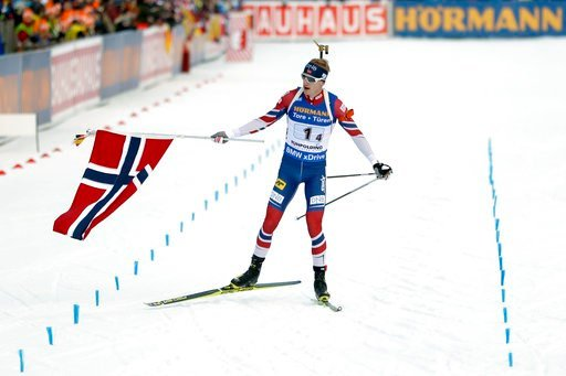 (AP Photo/Matthias Schrader). Johannes Thingnes Boe of Norway waves the national flag as he crosses the finish line to win the men's 4x7.5km relay competition at the biathlon World Cup in Ruhpolding, Germany, Friday, Jan. 12, 2018.