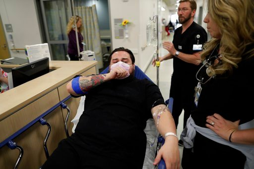 (AP Photo/Gregory Bull). In this Jan. 10, 2017 image, Donnie Cardenas recovers from the flu at the Palomar Medical Center in Escondido, Calif., on Wednesday, Jan. 10, 2018. The San Diego County resident said he was battling a heavy cough for days befor...