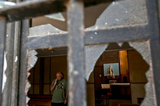 (AP Photo/Esteban Felix). A church employee surveys the damage caused by an overnight fire bomb attack at the Emmanuel Catholic Church, in Santiago, Chile, Friday, Jan. 12, 2018. Three churches were attacked with fire bombs in Santiago overnight, dropp...