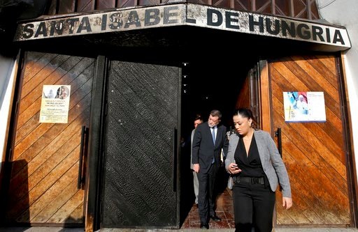 (AP Photo/Esteban Felix). Deputy Interior Secretary Aleuy Mahmud, center, exits the Santa Isabel de Hungria Catholic Church, past a door damaged in an overnight fire-bomb attack, in Santiago, Chile, Friday, Jan. 12, 2018. On the eve of a papal visit, v...