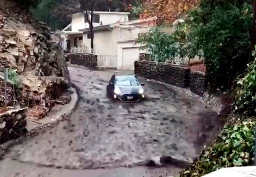 (Eric Frowley/Burbank Firefighters Local 778 via AP). In this image from video provided by Eric Frowley with Burbank Firefighters Local 778 a a car rides a wave of water, mud and rocks down a street in Burbank Calif., Thursday, Jan. 11, 2018. The drive...