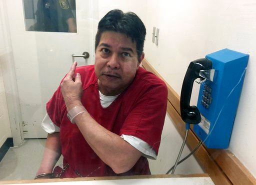 (AP Photo/Terry Chea, File). FILE - In this Nov. 17, 2017, file photo, escaped hospital patient Randall Saito points to a guard as he sits in an inmate visitor's booth at San Joaquin County Jail before a scheduled court hearing in French Camp, Calif. C...