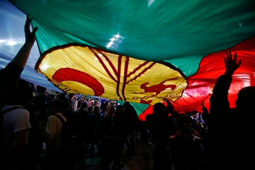 (AP Photo/Luis Hidalgo, File). FILE - In this Sept. 26, 2017 photo, demonstrators sustain afloat the Mapuche nation's flag during a protest against the arrests of several Mapuches, in Santiago, Chile. Pope Francis will meet with indigenous groups durin...