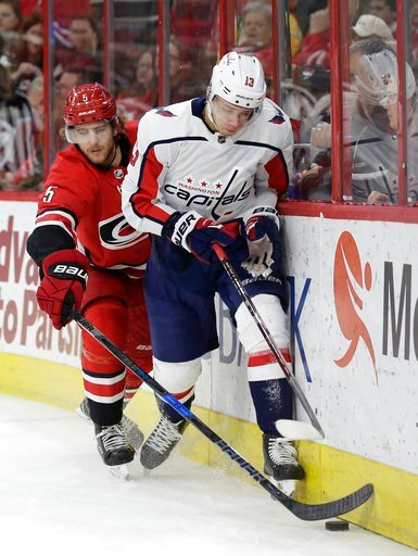 (AP Photo/Gerry Broome). Washington Capitals' Jakub Vrana (13), of the Czech Republic, and Carolina Hurricanes' Noah Hanifin (5) skate for the puck during the first period of an NHL hockey game in Raleigh, N.C., Friday, Jan. 12, 2018.