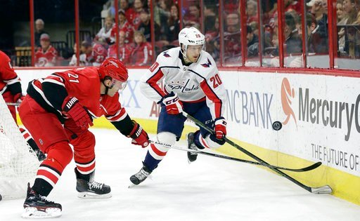 (AP Photo/Gerry Broome). Washington Capitals' Lars Eller (20), of Denmark, and Carolina Hurricanes' Lee Stempniak (21) chase the puck during the first period of an NHL hockey game in Raleigh, N.C., Friday, Jan. 12, 2018.