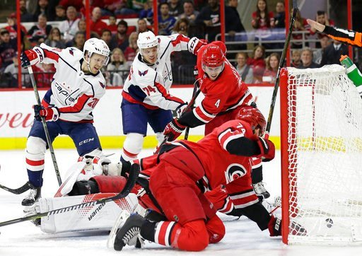 (AP Photo/Gerry Broome). Washington Capitals' Lars Eller (20), of Denmark, assists as John Carlson (74) scores against Carolina Hurricanes goalie Cam Ward while Hurricanes' Haydn Fleury (4) and Jaccob Slavin defend during the first period of an NHL hoc...