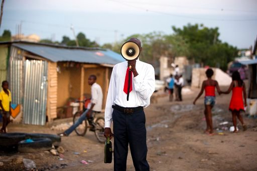 (AP Photo/Dieu Nalio Chery). In this Sunday, Jan. 7, 2018 photo, a bullhorn preacher evangelizes to the passing residents of the Caradeux refugee camp set up nearly eight years ago for people displaced by the 2010 earthquake, in Port-au-Prince, Haiti. ...