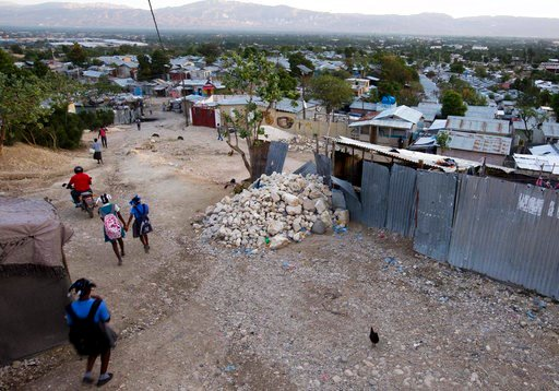 (AP Photo/Dieu Nalio Chery). In this Wednesday, Jan. 10, 2018 photo, children walk to the nearby school constructed inside the Caradeux refugee camp set up nearly eight years ago for people displaced by the 2010 earthquake, in Port-au-Prince, Haiti. Th...