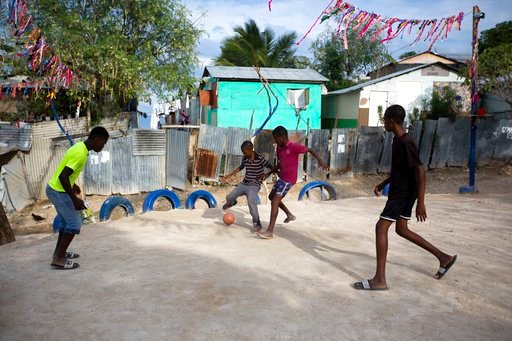 (AP Photo/Dieu Nalio Chery). In this Wednesday, Jan. 10, 2018 photo, boys play a pickup game of soccer on a pitch carved out at the Caradeux refugee camp set up nearly eight years ago for people displaced by the 2010 earthquake, in Port-au-Prince, Hait...