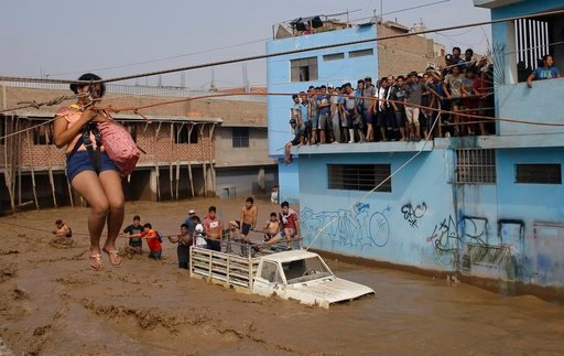 (AP Photo/Martin Mejia, File). FILE - In this March 17, 2017 file photo, a woman is pulled to safety in a zipline harness in Lima, Peru. Pope Francis specifically wants to visit Trujillo and the northern area hard hit by floods and mudslides last March...