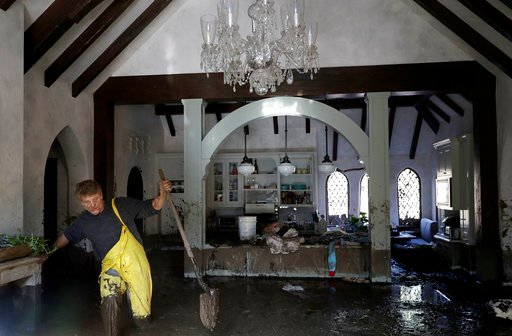(AP Photo/Marcio Jose Sanchez). Bill Asher walks through mud in his home damaged by storms in Montecito, Calif., Thursday, Jan. 11, 2018. Rescue workers slogged through knee-deep ooze and used long poles to probe for bodies Thursday as the search dragg...