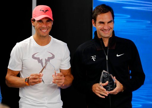 "(AP Photo/Vincent Thian). Spain's Rafael Nadal, left, and Switzerland's Roger Federer hold their trophies for International tennis Writers Association ""Ambassadors of the Year"" awards at a press conference at the Australian Open tennis championships in..."
