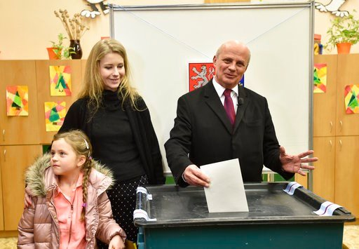 (Ondrej Hajek/CTK via AP). Presidential candidate Michal Horacek casts his vote as his we wife Michaela and daughter Julie look on during the presidential election's first round vote in Roudnice nad Labem (50 kilometres/31 miles North of Prague), on Fr...