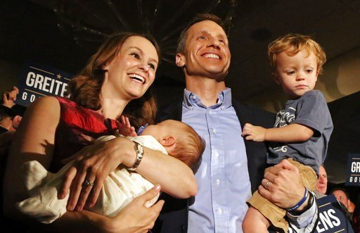 (J.B. Forbes/St. Louis Post-Dispatch via AP). In this Aug. 2, 2016, photo, Eric Greitens poses with his wife, Sheena and his two sons Jacob and Joshua at a watch party at the Doubletree Hotel in Chesterfield, Mo., after he was declared the winner in th...