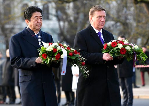 (AP Photo/Roman Koksarov). Japanese Prime Minister Shinzo Abe, left, and Latvian Prime Minister Maris Kucinskis lay flowers at the Freedom Monument in Riga, Latvia, Saturday, Jan. 13, 2018. Abe is on a visit to three Baltic countries, Estonia, Latvia a...