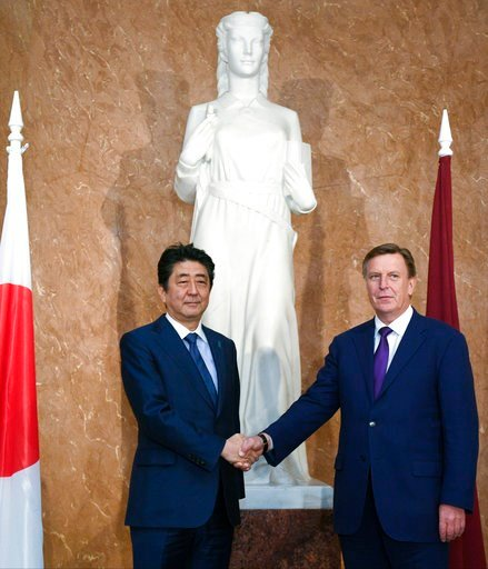(AP Photo/Roman Koksarov). Japanese Prime Minister Shinzo Abe, left, and Latvian Prime Minister Maris Kucinskis shake hands as they pose for a photo prior to their talks in Riga, Latvia, Saturday, Jan. 13, 2018. Abe is on a visit to three Baltic countr...