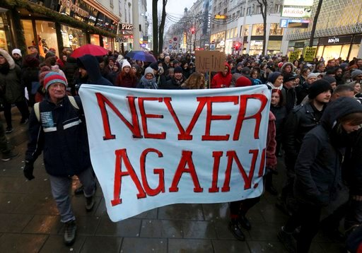 (AP Photo/Ronald Zak). Protesters walk during a demonstration against the new Austrian government in Vienna Austria, Saturday, Jan. 13, 2018.