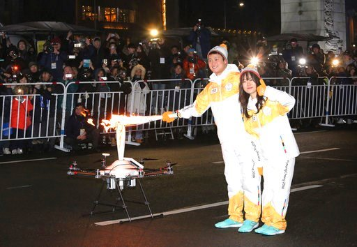 (AP Photo/Ahn Young-joon). Torch bearers pose as they pass the Olympic flame to a drone during the Olympic Torch Relay in Seoul, South Korea, Saturday, Jan. 13, 2018. South Korea said Saturday that North Korea proposed that their talks next week addres...
