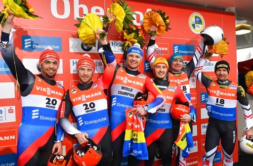 (Martin Schutt/dpa via AP). From left: Germany's second placed Tobias Wendl, and Tobias Arlt,  German winners Toni Eggert and Sascha Benecken and Austria's third placed Peter Penz and Georg Fischler  celebrate after the men's doubles at the Luge World ...