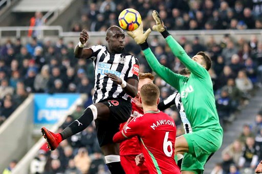 (Owen Humphreys/PA via AP). Newcastle United's Mohamed Diame, left, heads towards goal during the English Premier League soccer match against Swansea City at St James' Park, Newcastle, England, Saturday Jan. 13, 2018.