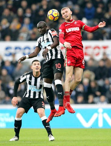 (Owen Humphreys/PA via AP). Newcastle United's Mohamed Diame, center, and Swansea City's Oliver McBurnie battle for a header during the English Premier League soccer match against Swansea City at St James' Park, Newcastle, England, Saturday Jan. 13, 20...