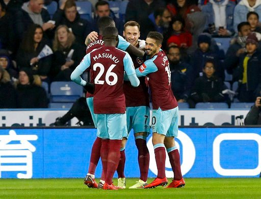 (Martin Rickett/PA via AP). West Ham United's Marko Arnautovic, facing, celebrates scoring his side's second goal of the game against Huddersfield Town with teammates during the English Premier League soccer match against West Ham United at the John Sm...