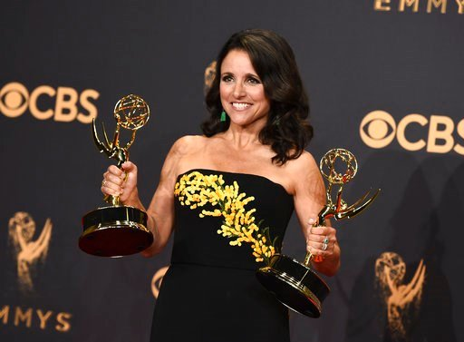 "(Photo by Jordan Strauss/Invision/AP). FILE - In this Sunday, Sept. 17, 2017 file photo, Julia Louis-Dreyfus poses in the press room with her awards for outstanding lead actress in a comedy series and outstanding comedy series for ""Veep"" at the 69th Pr..."